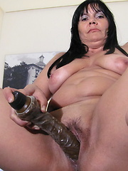 Busty mom puts huge dildo into her sweet hole