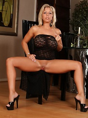 Amber Lynn Bach strips from her black dress and fucks her wet pussy with a big dildo.